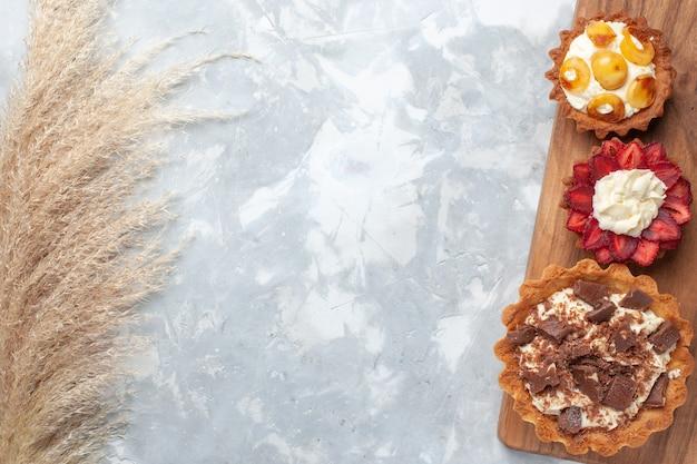 Vue de dessus différents gâteaux crémeux au chocolat et fruits sur gâteau de bureau blanc cuire au four biscuit sucre sucré