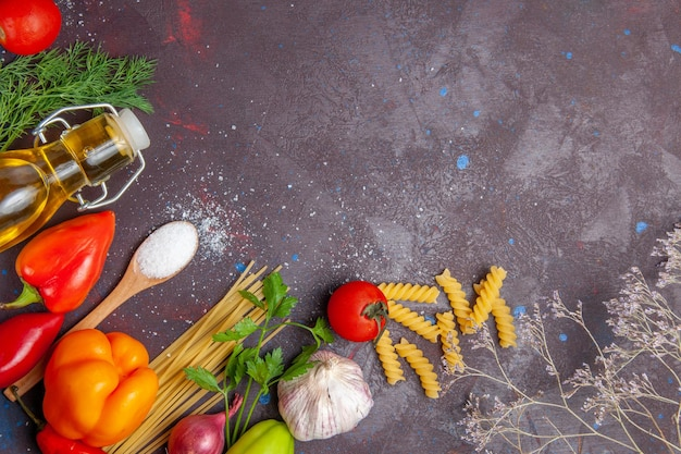 Vue de dessus différents ingrédients pâtes crues et légumes frais sur fond sombre produit alimentaire santé salade régime