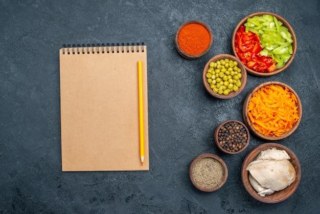 Vue de dessus différents ingrédients de la salade avec du poulet sur une table sombre régime alimentaire santé repas
