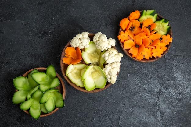 Vue de dessus différents légumes conçus à l'intérieur de pots sur un espace gris