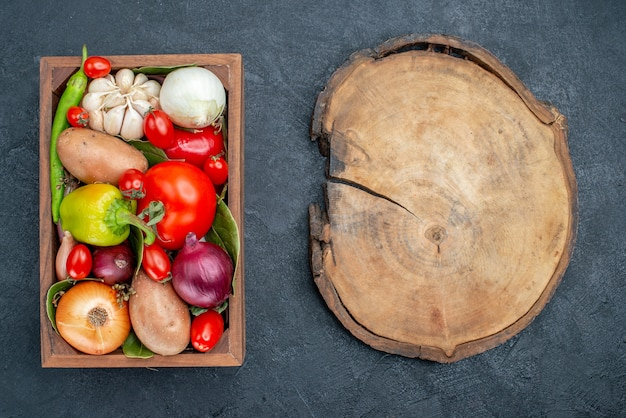 Vue de dessus différents légumes frais sur un sol sombre salade fraîche de légumes mûrs