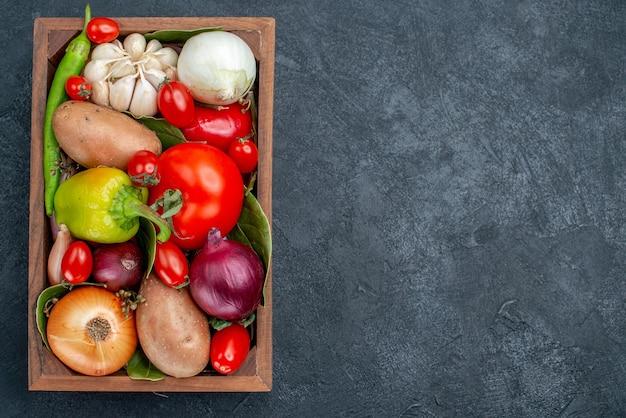 Vue de dessus différents légumes frais sur la table sombre salade de légumes frais mûrs