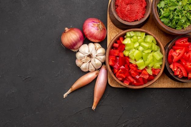 Vue de dessus différents légumes avec des verts sur fond gris foncé salade repas santé mûr épicé