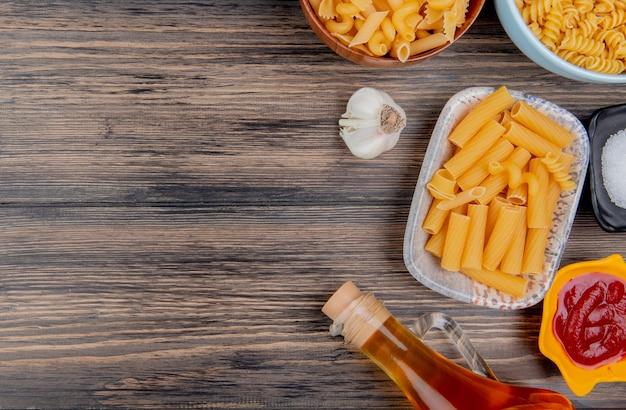 Vue de dessus de différents macaronis comme ziti rotini et autres avec du beurre fondu à l'ail, sel et ketchup sur bois avec espace de copie