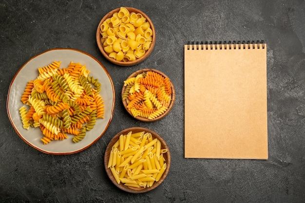 Vue de dessus de différents produits bruts de composition de pâtes à l'intérieur des assiettes sur fond gris