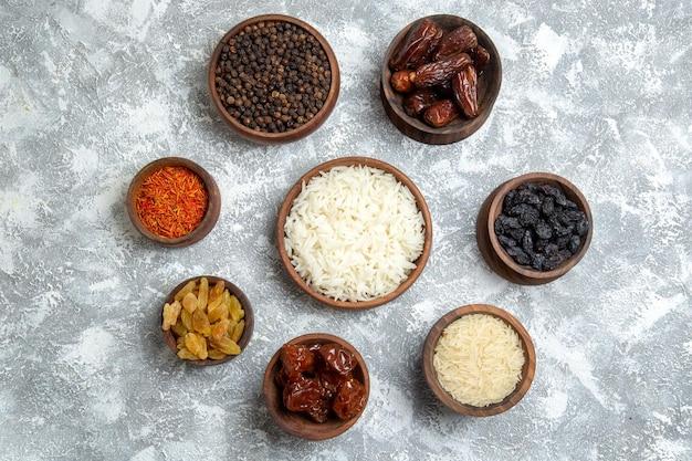 Vue de dessus différents raisins secs avec assaisonnements et riz sur un espace blanc