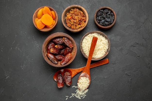 Vue de dessus différents raisins secs avec du riz cru sur la surface sombre des raisins secs aux fruits secs crus