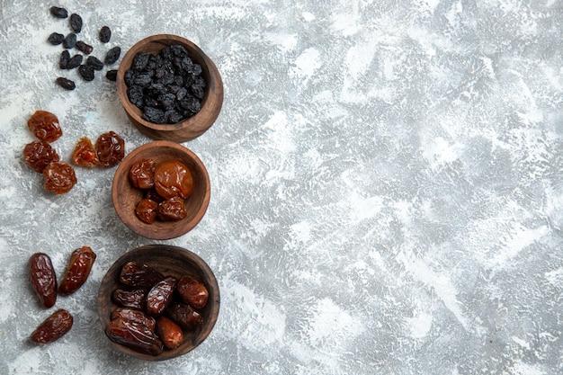 Vue de dessus différents raisins secs à l'intérieur de petits pots sur un espace blanc