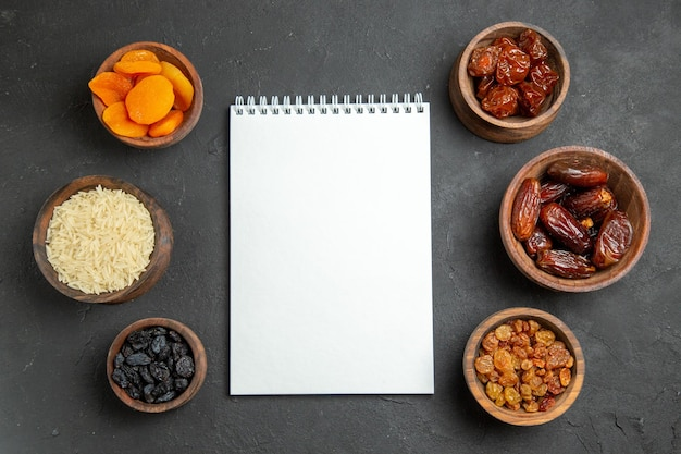 Vue de dessus différents raisins secs à l'intérieur de pots sur une surface sombre aux fruits secs khurma raisin sec
