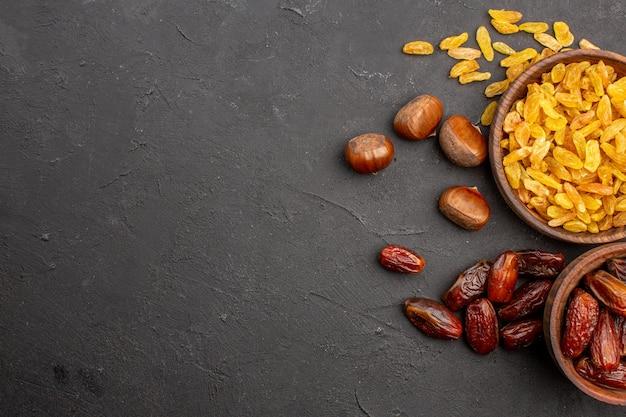 Vue de dessus de différents raisins secs savoureux du raisin et d'autres fruits sur la surface grise