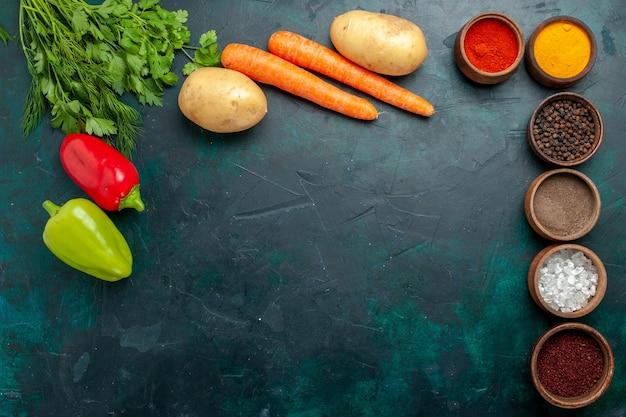 Vue de dessus différents seasonigns avec des légumes frais sur fond vert foncé ingrédient produit repas alimentaire légume