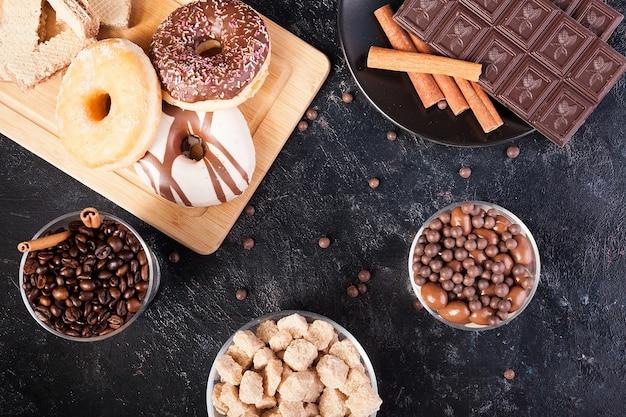 Vue de dessus de différents types de bonbons et de pâtisseries sur fond de bois vintage foncé