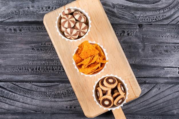 Vue de dessus de différents types de collations comme des biscuits et des frites dans des bols sur une planche à découper sur une surface sombre horizontale