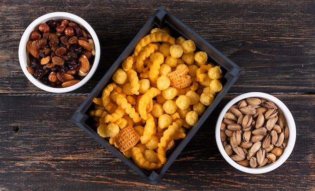 Vue de dessus de différents types de collations comme des boulettes de maïs dans une caisse noire et des noix avec des fruits secs, des pistaches dans des bols sur une surface en bois sombre horizontal