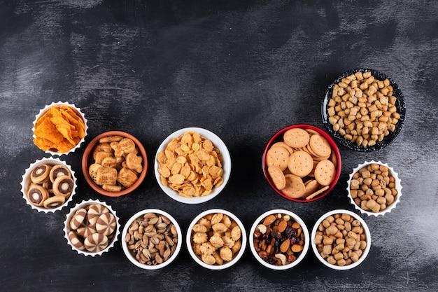 Vue de dessus de différents types de collations comme les noix, les craquelins et les biscuits dans des bols avec copie espace sur une surface sombre horizontale