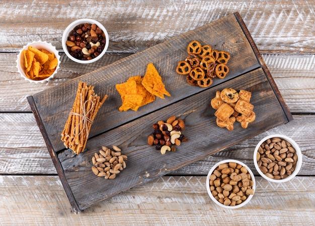 Vue de dessus de différents types de collations comme les noix, les craquelins et les biscuits sur une surface en bois blanche horizontale