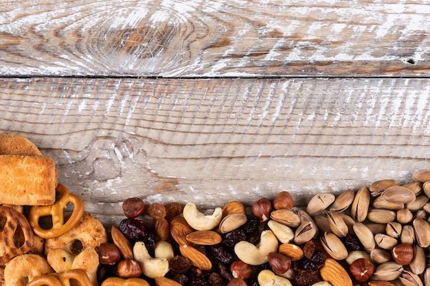 Vue de dessus de différents types de collations comme les noix, les craquelins et les cookies avec copie espace sur fond de bois blanc horizontal