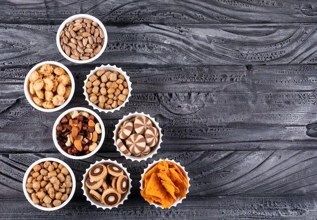 Vue de dessus de différents types de collations comme les noix, les craquelins et les cookies dans des bols avec copie espace sur fond sombre horizontal
