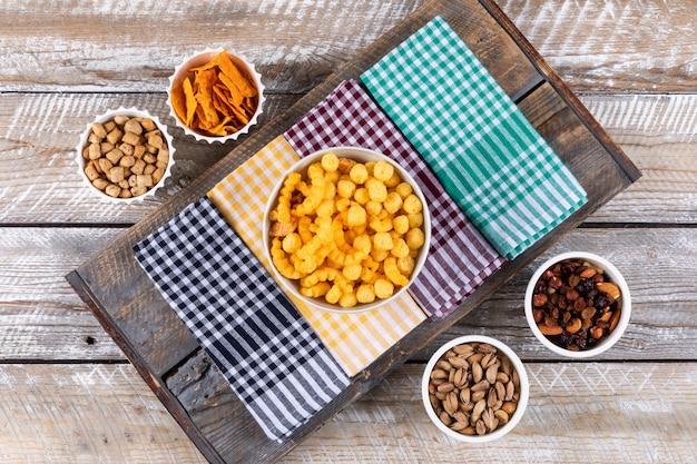 Vue de dessus de différents types de collations comme les noix, les craquelins et les cookies sur des serviettes sur une surface en bois blanche horizontale