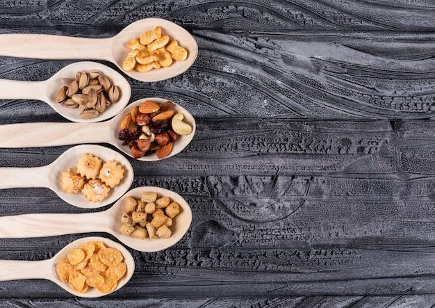Vue de dessus de différents types de collations comme des noix et des craquelins sur des cuillères en bois avec copie espace sur fond sombre horizontal