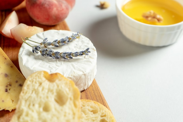 Vue de dessus différents types de fromages sur une planche à découper en bois. fromage à la figue pêche, miel, ciabatta et noix, verre de vin rouge. plat élégant plat posé sur fond gris. copiez l'espace. flou artistique