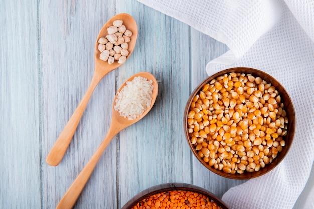 Vue de dessus de différents types de gruaux et de graines dans des bols et des cuillères en bois, lentilles rouges, graines de maïs, riz et pois chiches