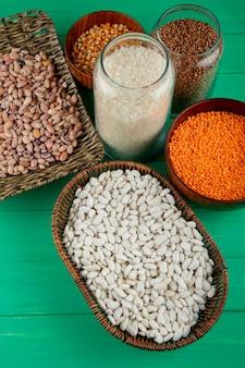 Vue de dessus de différents types de légumineuses et céréales lentilles rouges haricots sarrasin et grains dans des bocaux en verre et des paniers en osier