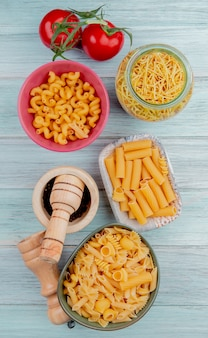 Vue de dessus de différents types de macaronis comme spaghetti cavatappi ziti avec sel de tomate poivre noir sur bois