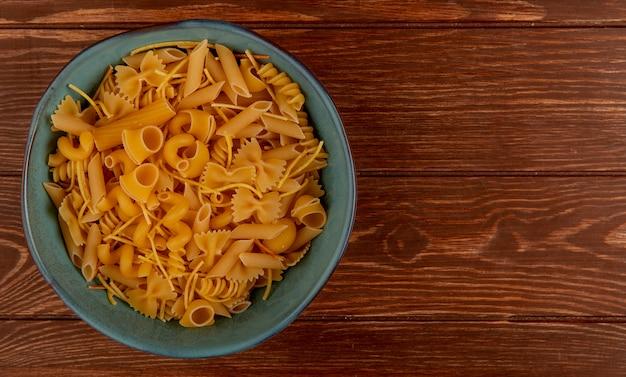 Vue de dessus de différents types de macaronis dans un bol sur bois avec espace copie