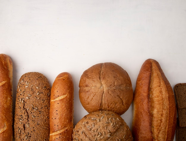 Vue de dessus de différents types de pain comme seigle baguette cob sur fond blanc avec copie espace