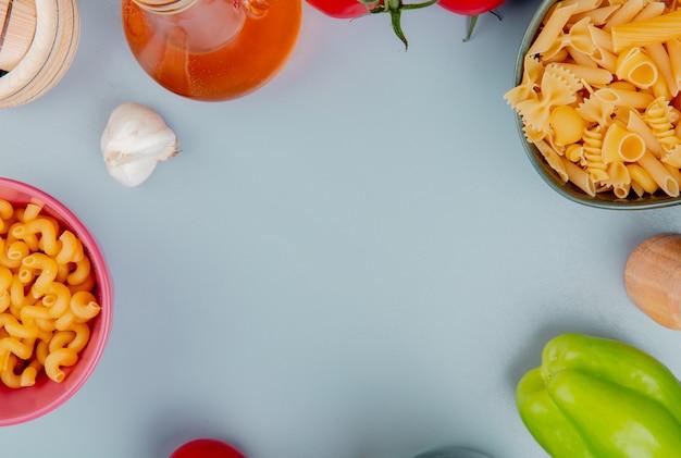 Vue de dessus de différents types de pâtes comme pipe-rigate cavatappi et d'autres avec du sel au poivre au beurre à l'ail sur la surface bleue avec copie espace