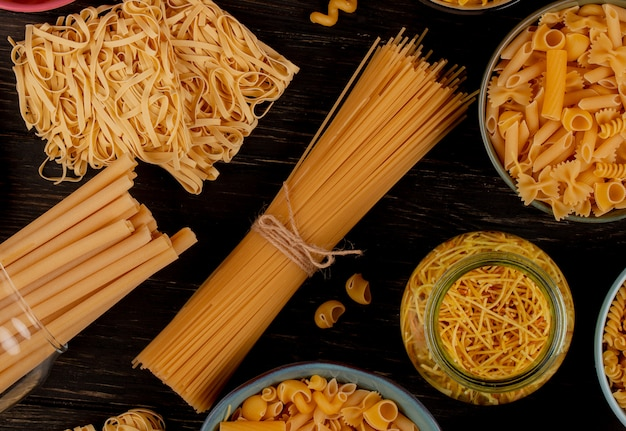Vue de dessus de différents types de pâtes comme les tagliatelles de spaghetti de vermicelles de bucatini et d'autres sur la surface en bois