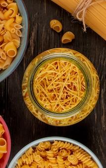 Vue de dessus de différents types de pâtes comme les vermicelles rotini et autres en pot et bols sur une surface en bois