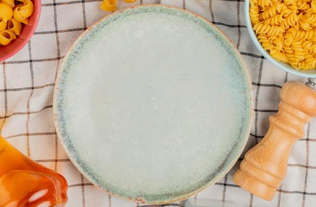 Vue de dessus de différents types de pâtes dans des bols de beurre de sel autour de la plaque sur la surface de tissu à carreaux
