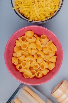 Vue de dessus de différents types de pâtes dans des bols comme tagliatelle bucatini pipe-rigate sur la surface bleue