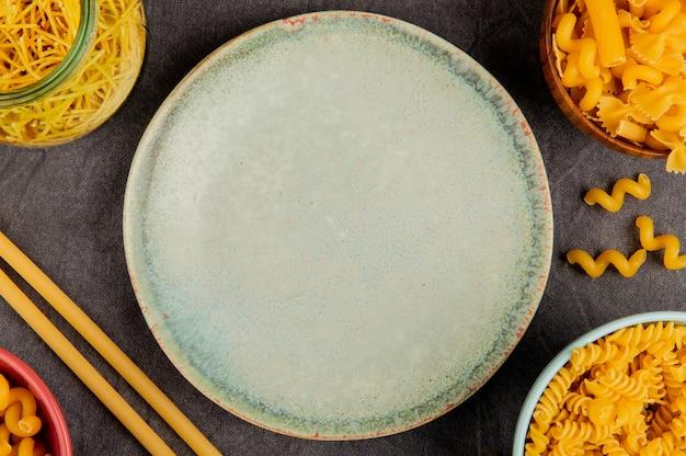 Vue de dessus de différents types de pâtes en pot et bols autour de la plaque sur une surface en tissu gris