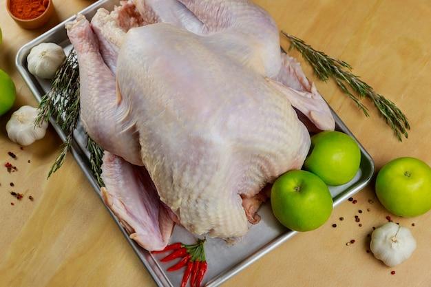 Vue de dessus de la dinde crue de thanksgiving ou de noël avec des herbes, de l'ail et des pommes sur fond de bois.