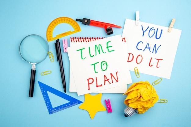 Vue de dessus divers articles de bureau règles lupa stylo dessin boussole temps à planifier et vous pouvez le faire écrit sur des papiers sur fond bleu