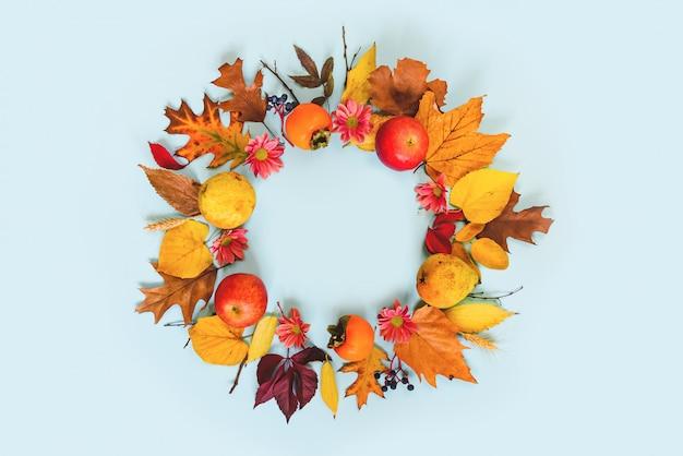 Vue de dessus de divers fruits et feuilles d'automne colorés dans un panier en osier sur une table bleu clair.