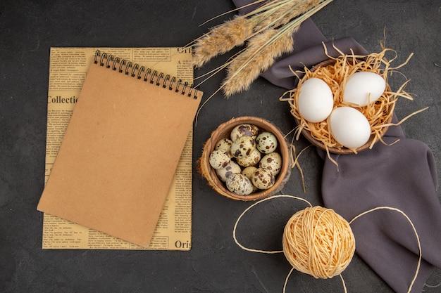 Vue de dessus de divers œufs biologiques dans un cahier à spirale de serviette noire à pointe de corde de pot marron sur un vieux journal sur fond sombre