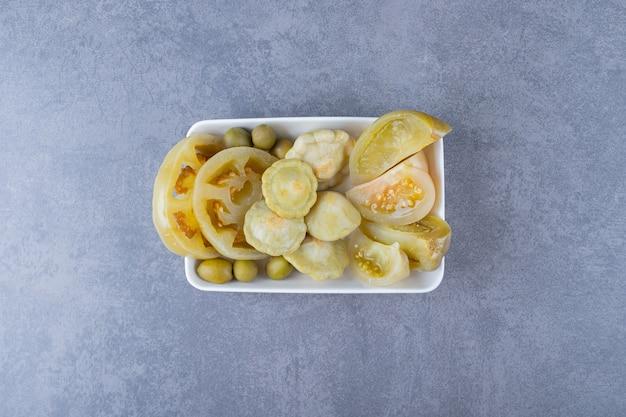 Vue de dessus de divers types de cornichons de légumes sur une plaque blanche.