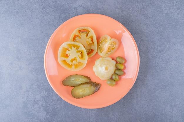 Vue de dessus de divers types de cornichons de légumes sur une plaque orange.