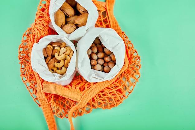 Vue de dessus de divers types d'écrous sur la table dans un sac en papier dans le sac d'épicerie sur la surface verte