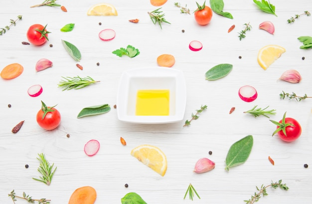 Vue de dessus de divers types de feuilles d'herbes aromatiques et légumes coupés sur table en bois