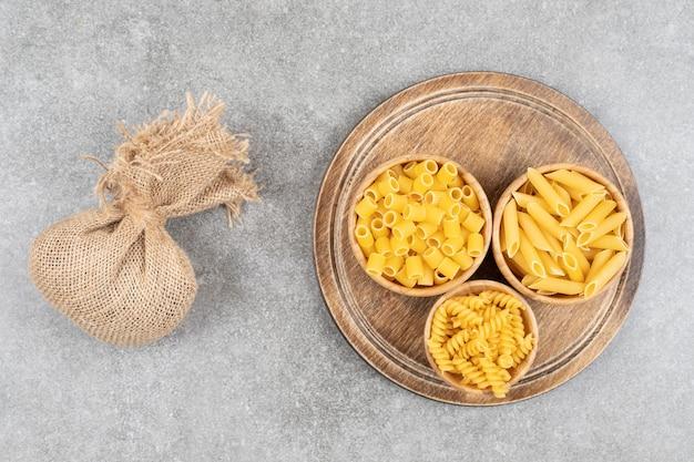 Vue de dessus de divers types de pâtes dans un bol sur une planche de bois.