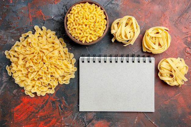 Vue de dessus de divers types de pâtes non cuites et cahier sur fond de couleur mixte