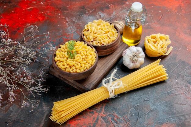Vue de dessus de divers types de pâtes non cuites sur une planche à découper en bois et une bouteille d'huile d'ail sur fond de couleur mixte