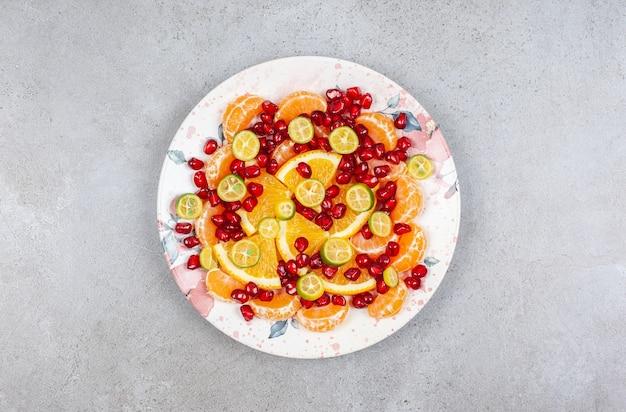 Vue de dessus de divers types de tranches de fruits sur assiette.