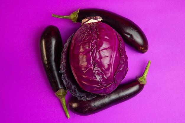 Vue de dessus de diverses aubergines de légumes frais et chou rouge sur violet
