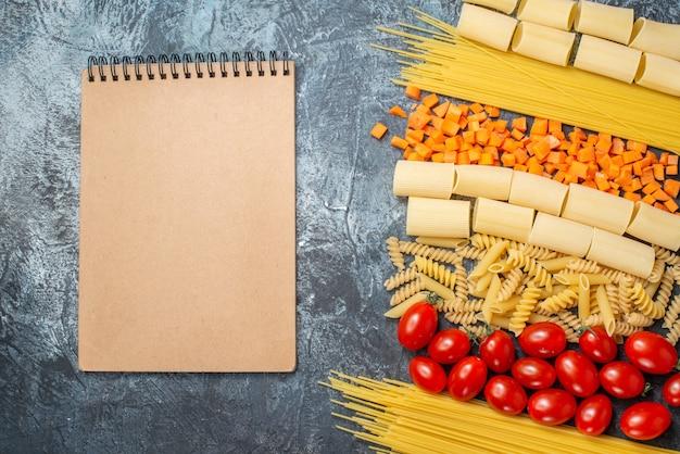 Vue de dessus diverses pâtes rigatoni spaghetti penne spirales tomates cerises carottes hachées bloc-notes sur fond gris